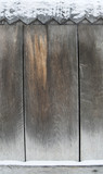 old dark wooden fence in snow. wood background