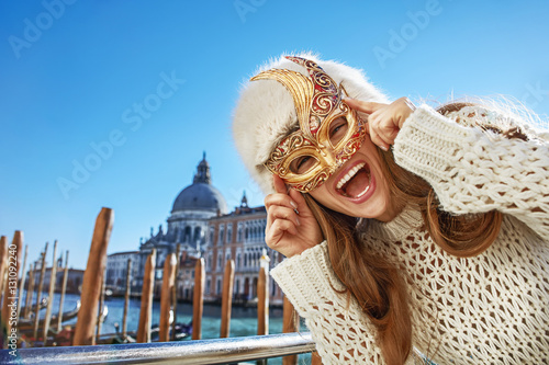 Portrait of happy woman in Venice, Italy wearing Venetian mask