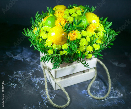 Foto op Canvas In het ijs Bouquet with roses, lemons and a lime in a wooden box. The isolated object on a dark background. Fruits and flowers