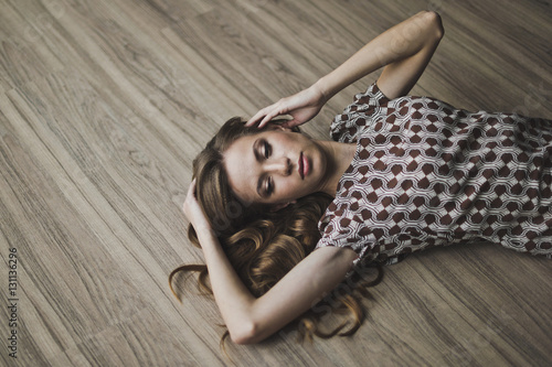 Obraz The girl lay on the parquet floor, arms outstretched 6963. - fototapety do salonu