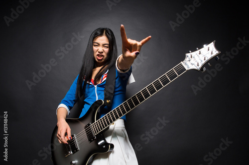 Fotografie, Obraz  Asian rock star lady showing yo sign while playing guitar isolated on grey background in studio