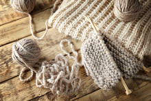 Knitting Yarn And Needles On Wooden Background, Closeup
