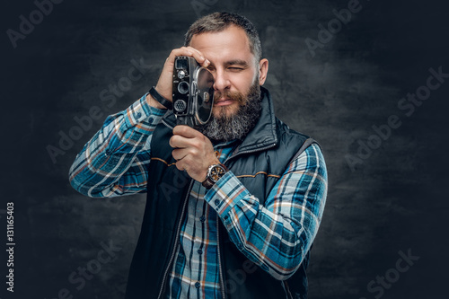 Fotografie, Obraz  Bearded middle age male holds vintage 8 mm video camera.