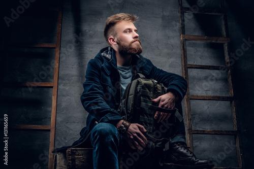 Fotografie, Obraz  The bearded backpacker male sits on a wooden box.
