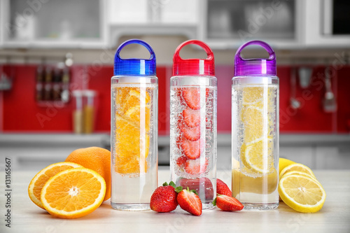 Fototapeta Bottles with fruit-infused water on kitchen table