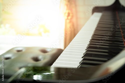 Obraz na plátne  Piano keys with yellow flare light in the window