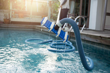 Man Cleaning Swimming Pool Wit...