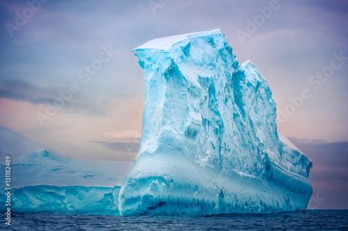 Foto auf Gartenposter Antarktika Antarctic iceberg of unusual form in the snow floating in open ocean. Pastel sunset sky in the background. Beauty world.
