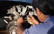 Mechanic repairing disk break with spraying oil