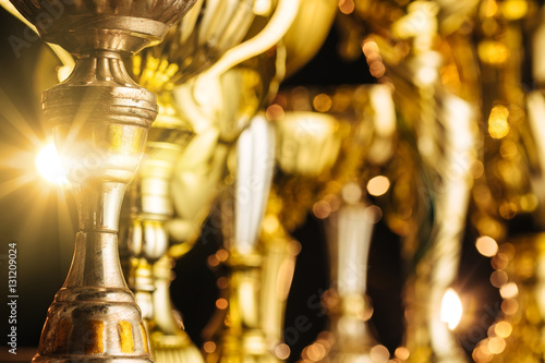 Fotografía  Group of the golden trophies in sparkling light on the dark background