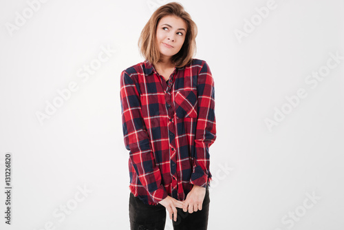Fotografie, Obraz  Charming shy woman in plaid shirt standing and looking away