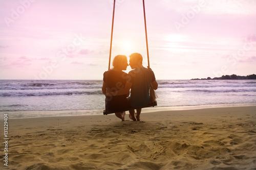 Fotografia Romantyczna para siedzi i całuje się na plaży morza na huśtawce liny i patrząc na zachód horyzontu