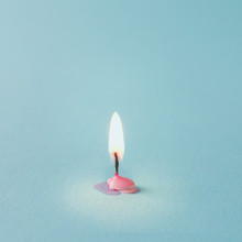 Burnt Out Pink Candle On Blue Background. Minimal Timeline Conce