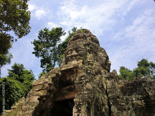 Bayon face carved in ancient abandoned lost temple in Siem Reap, Cambodia Poster