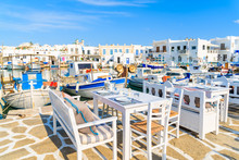 Greek Taverna Tables And Fishing Boats Anchoring In Naoussa Port, Paros Island, Greece