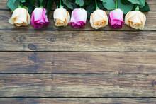 Seven Roses On A Wooden Backgr...