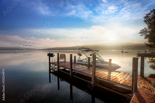Canvas Print Sunrise through the clouds and mist over a calm New Hampshire lake