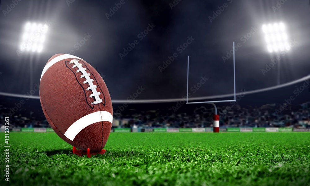 Fototapeta American football in stadium at night with spotlight