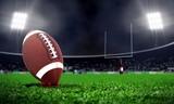 American football in stadium at night with spotlight