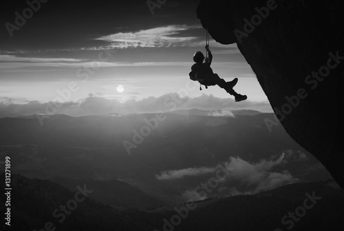 Climber against sunset background. Black and white