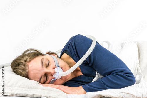 Woman sleeping  on her side with CPAP, sleep apnea treatment Canvas Print