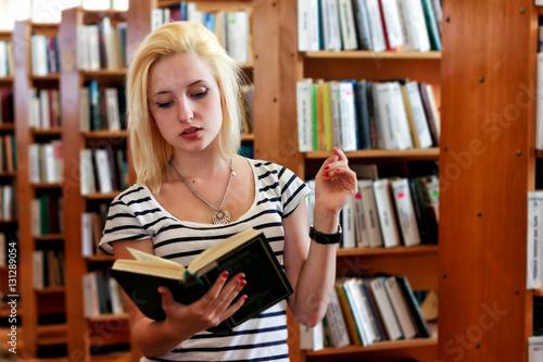 Keuken foto achterwand Berlijn Blonde girl reading book in front of full bookshelves