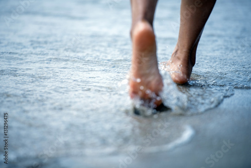 Woman barefoot walking on the beach Wallpaper Mural