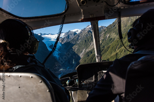 Poster Helicopter Passengers in a helicopter as it approaches the Franz Josef Glacier in New Zealand