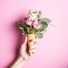 Beautiful Flower In Ice Cream Cone In Girls Hand With Manicure On Pink Background