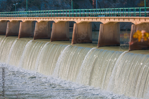 Photo Stands Dam Strong stream of water at the hydroelectric dam