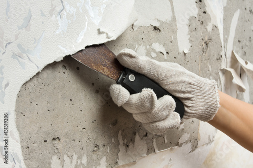 Fotografie, Obraz  hand removing wallpaper from wall with spatula