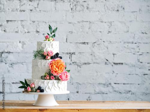 Zdjęcie XXL Biały ślubny tort z kwiatami i czarnymi jagodami