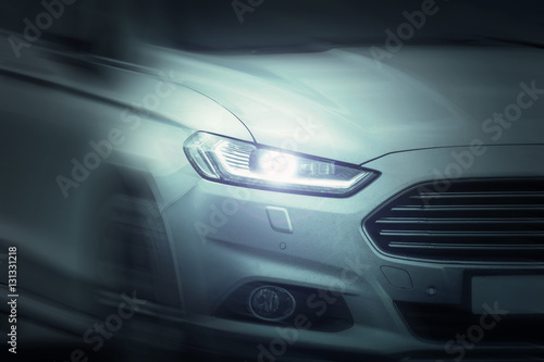 Spoed Foto op Canvas Stadion White sport car ride on road motion blur. Xenon and angel eyes headlamps