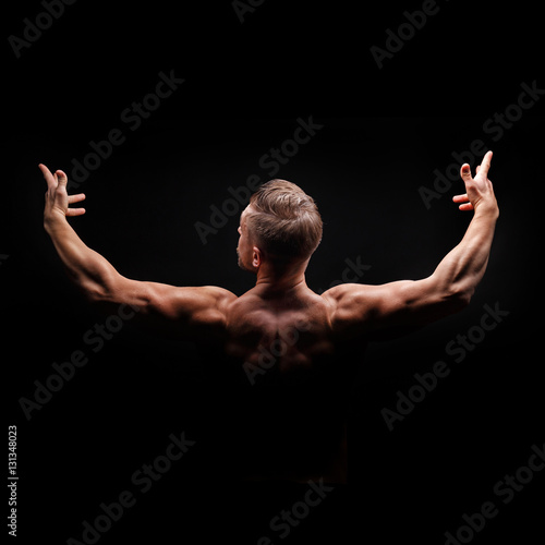 Foto op Plexiglas Fitness Bodybuilder posing on a black background. Dramatic portrait of an athlete. Drying. Relief and sculptural muscles of the body. Healthy lifestyle concept. The muscles of the shoulders.