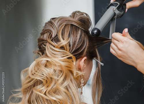Photo Closeup hairdresser coiffeur makes hairstyle.