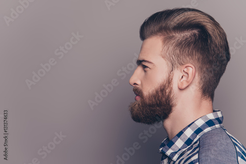 Valokuva  Side view portrait of handsome thinking stylish young man lookin