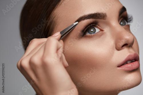Valokuva  Beautiful Woman Plucking Eyebrows. Beauty Brows Correction
