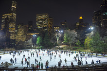 Skaters Take Advantage Of A Mild Night At An Ice Skating Rink In Central Park Against The Midtown, Manhattan New York City Skyline