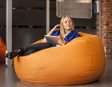 Armchair Traditional Bean Bag For Fun And Relaxation  Orange Color. Young Woman  Using Tablet Screen While Sitting On Big Cushioned Frameless Chair