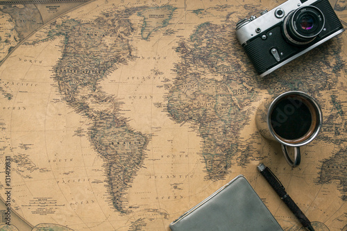 Vintage Camera, Notebook, Pen, Metal Coffee Cup on Retro World Map Poster