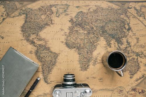 Foto  Vintage Camera, Notebook, Pen, Metal Coffee Cup on Retro World Map