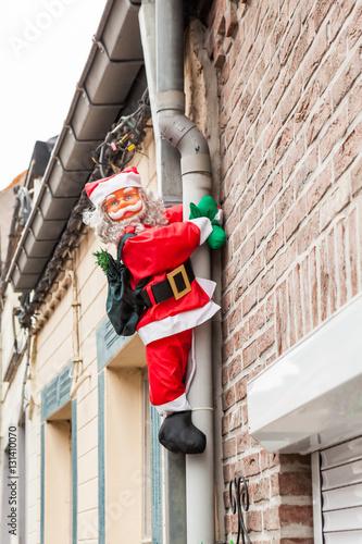 Valokuva  Santa hanging on the drainpipe