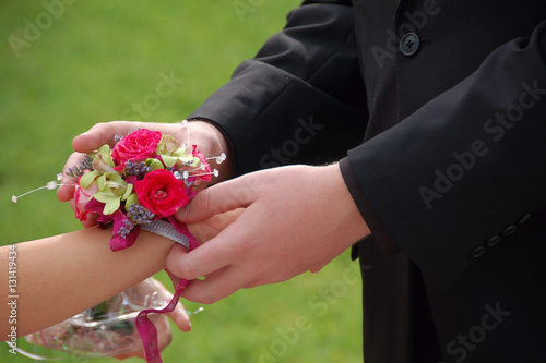 Photo Young man slides wrist corsage onto prom date