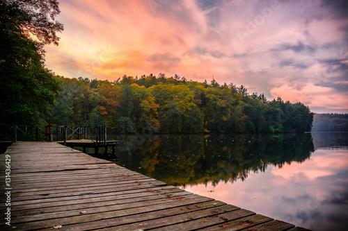 Zachód słońca z pomostu przy zamku nad Jeziorem Trześniowskim jesienią w Łagowie, woj. Lubuskie.