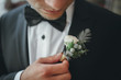 canvas print picture - young groom boutonniere in his hand closeup