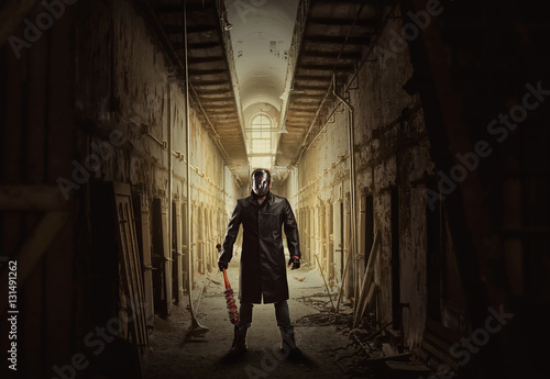Photo Killer with bloody bat in abandoned building.