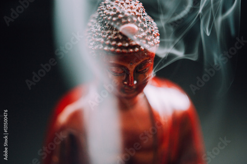 Tuinposter Boeddha Buddha statue with incense. Deity and symbols of Buddhism. The practice of Buddhism and its symbols. Spiritual life of Asia