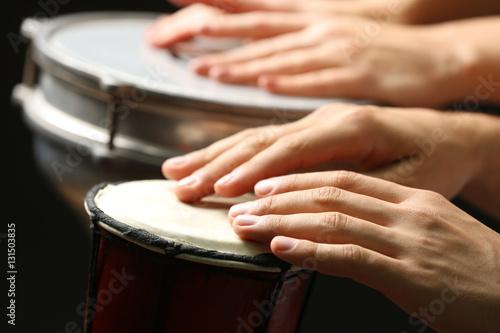 Fotografía  Hands of man playing African drum on dark background, close up