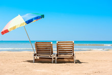 Two Wooden Beach Chairs And Umbrella On Tropical Ocean Beach At Sunny Summer Day