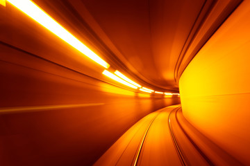 Speed motion blurred underground subway tunnel yellow color toned